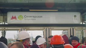 View of table on entrance of new metro station with writing Seligerskaya. Crowd of people waiting for opening new metro station stock footage