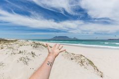 View of Table Mountain from Blouberg in Cape Town with hand and travel tattoo. View of Table Mountain from Blouberg in Cape Town with hand and windsurfers royalty free stock photos