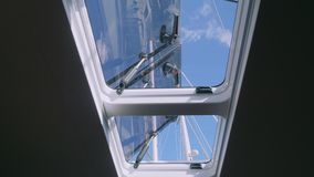 View of tackle and mast of yacht through window of yacht cabin stock footage