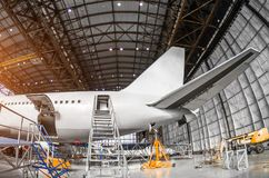 View of the tail passenger aircraft on service in an aviation hangar rear, ladder entrance stock image