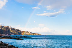 View of Taormina cape and rainbow in Ionian Sea Stock Image