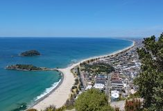View of Tauranga from Mount Maunganui in New Zealand. Many people are on the beach enjoying the perfect weather stock image