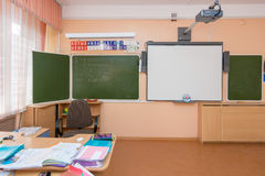 A view of the teacher`s desk and blackboard in elementary school classroom. Anapa, Russia - February 28, 2017: A view of the teacher`s desk and blackboard in Royalty Free Stock Photography