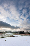 View from tee on a snowy golf course in winter. View from the tee of a golf course in Scotland on a snowy winter morning, with dramatic cloudy sky overhead Stock Images