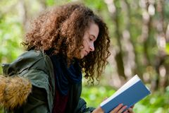 Teen girl reading book in autumn park Royalty Free Stock Image