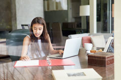 View Of Teenage Girl Using Laptop Through Window Stock Image
