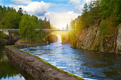 View of the Telemark Canal with old locks - tourist attraction in Skien, Norway. Bridge above the river and waterfall. View of the Telemark Canal with old locks stock photos