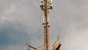 A view of a television tower against of the blue sky with clouds. A view of a television tower from bottom to the top against of the blue sky with clouds stock video footage