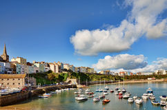 View of Tenby harbour against a blue summer sky. Sweeping view of Tenby harbour with boats, on a summers day with a vivid blue sky and cumulus clouds Royalty Free Stock Images