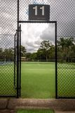View of a tennis court through the open gate in a fence to the court stock images