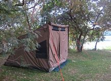 TENT ON A CAMPSITE NEXT TO A RIVER. View of a tent on the lawn in a camping site next to a river with green trees and foliage royalty free stock photo