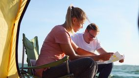 Two campers looking at local map. View from the tent to the man and woman campers exploring map sitting by the river. Searching for the best places to hike and stock footage