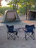 CAMPSITE IN AFRICAN WILDERNESS. View of tents and camping chairs in a campsite in a park in the wilderness of Africa royalty free stock photos