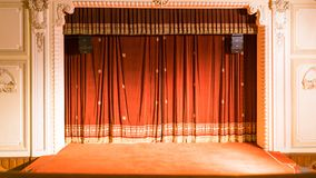 View from within a theater with stage chairs and curtain stock images