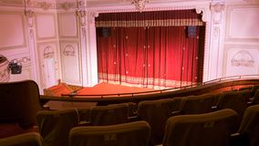 View from within a theater with stage chairs and curtain stock image