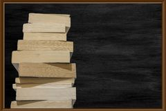 View of thick books lined up in a row and black chalk board in background.  stock photos