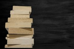 View of thick books lined up in a row and black chalk board in background.  stock image