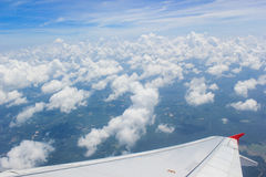 A view though an airplane window where one can see the wing and beautiful cloudy sky Royalty Free Stock Photography