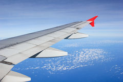 A view though an airplane window where one can see the wing and beautiful cloudy sky Royalty Free Stock Photo