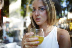 View though the window of a attractive female drinking a glass of fresh orange juice, young happy caucasian woman enjoying natural Stock Image