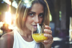 View though the window of a young gorgeous woman enjoying a natural fruit juice and looking at you Royalty Free Stock Images