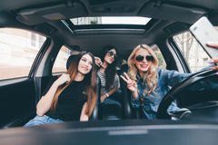 View of Three beautiful young cheerful women making selfie and smiling while sitting in car together Stock Photography