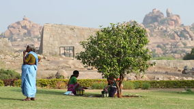 View of three women on the grass, two sitting under the tree, third standing. HAMPI, INDIA - 28 JANUARY 2015: View of three women on the grass, two sitting stock footage