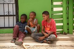 Three Amigos Having a Good Time. A view of three young Dominican boys watching some friends play in the village of El Monte Rey stock photo