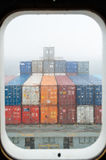 View throught the porthole of a container ship Stock Photography