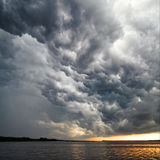 View of thunderstorm clouds. Above water Stock Images