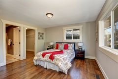 View of tidy bedroom with hardwood floor. And colorful bed with red pillows. Has doors to the bathroom and empty closet. Northwest, USA Stock Photo