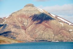 View to the abandoned Russian arctic settlement Pyramiden with the natural mountain in the form of pyramid above, Norway. stock photography