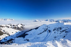 View to Alpine mountains surrounded by fog and ski slopes in Austria from Kitzbuehel ski resort Stock Image
