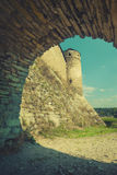 View to the ancient castle. View through the stone arch to the ancient castle. Sepia stylisation. Europe, Ukraine Stock Images