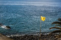 View to Atlantic Ocean and yellow flag on the Callao Salvaje beach. View to Atlantic Ocean and yellow flag on the Callao Salvaje beach, tenerife Stock Photo