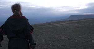 View to the back of knight that stands with sword and looks to horizon. In mountains stock video
