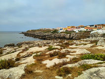 View to the bay with rocks and houses in cloudy evening light, Peniche Stock Images