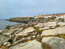 View to the bay with rocks and houses in cloudy evening light, Peniche Royalty Free Stock Images