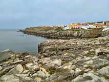 View to the bay with rocks and houses in cloudy evening light, Peniche Stock Photography