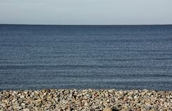 Blue Horizon as the pebbled beach and see meet the sky royalty free stock images