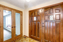 View to brown wooden enterance door. Tile floor and carpet floor in the next room. Royalty Free Stock Images