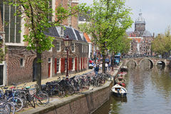 View to the canal with bicycles parked and basilica of Saint Nicholas at the background in Amsterdam, Netherlands. Stock Image