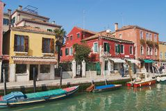 View to the channel, boats, buildings and people at the street in early spring in Murano, Italy. Stock Photos