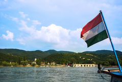 A view to a church at Visegrad, a small town at Hungary near Budapest from a ship at Danube. And a hungarian flag at the foreground Royalty Free Stock Image