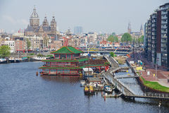 View to the city of Amsterdam with canal, historic buildings and basilica of Saint Nicholas in Amsterdam, Netherlands. Royalty Free Stock Image