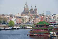View to the city of Amsterdam with canal, historic buildings and basilica of Saint Nicholas in Amsterdam, Netherlands. Stock Images