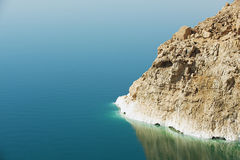 View to the cliff at the Dead sea shore with reflection in the water in Jordan. Stock Photo
