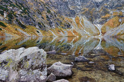View to Czarny staw pod Rysami, lake in Tatry mountains. October day in polish mountains, amazing reflections of grey rocks in shallow lake near Rysy mountain Stock Images