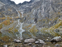 View to Czarny staw pod Rysami, lake in Tatry mountains. October day in polish mountains, amazing reflections of grey rocks in shallow lake near Rysy mountain Stock Photos