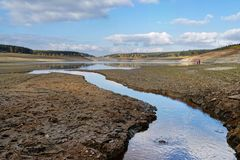 View to the dam wall of a dam with low water level, the dryness is clearly visible, consequence of the hot summer 2018 - Location royalty free stock image